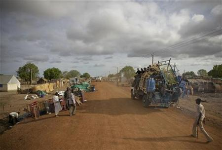 A truck carrying looted items passes by a street where more items waiting for collection line the edge of the road in Abyei town May 24, 2011. REUTERS/Stuart Price/UNMIS/Handout