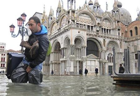 A man walks through flood waters in Saint Mark's Square during a period of high water, which happens periodically from high tides during the winter months, in Venice December 3, 2010. REUTERS/Manuel Silvestri