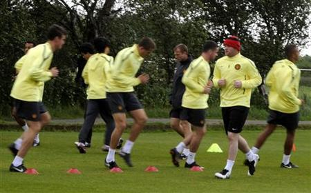 Manchester United's Wayne Rooney (2nd R) warms up with teammates during a practice session at the club's Carrington training ground in Manchester, northern England May 24, 2011. United plays Barcelona in the Champions League final at Wembley on Saturday. REUTERS/Nigel Roddis