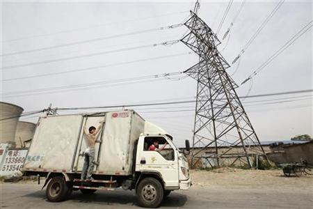A truck carrying a man drives past electricity wires near a coal-fired power plant, in Beijing May 24, 2011. REUTERS/Jason Lee