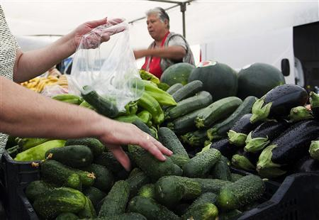 A woman buys cucumbers at a market in El Alquian, Almeria, in southeastern Spain, May 29, 2011. REUTERS/Francisco Bonilla
