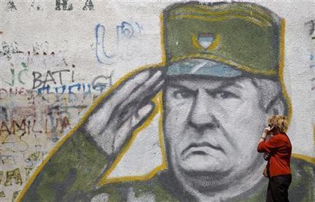 A woman walks past graffiti of Bosnian Serb wartime general Ratko Mladic in a suburb of Belgrade May 27, 2011. REUTERS/Stoyan Nenov