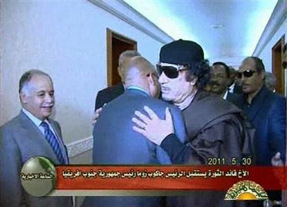Still image taken from a video distributed by Libyan state television shows Libyan leader Muammar Gaddafi hugging South African President Jacob Zuma after talks in Tripoli May 30, 2011. REUTERS/ Libya TV via Reuters TV