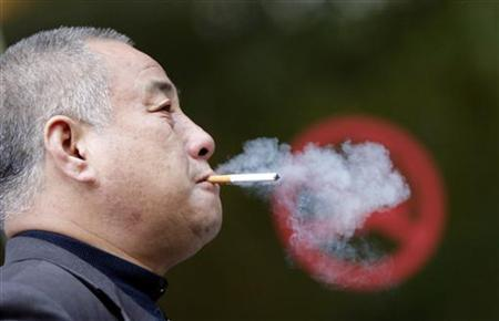 A man smokes next to a ''No Smoking'' sign in downtown Shanghai April 27, 2011. REUTERS/Carlos Barria