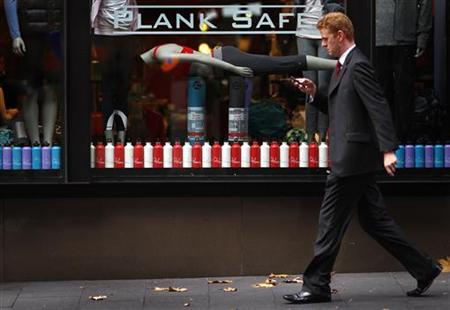 A pedestrian using a cell phone walks past a sports clothing shop window display of a mannequin planking, in Sydney May 31, 2011. Planking, the fad of lying face down stiff in often bizarre places for a photo op, has become a global craze. REUTERS/Tim Wimborne