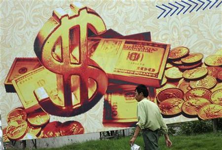 A man walks past a billboard featuring U.S. dollar notes on a street in Hefei, Anhui province July 8, 2010. REUTERS/Stringer