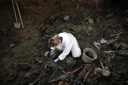 A forensic expert of the International Commission for Missing Persons (ICMP) searches for human remains in a mass grave in the village of Kamenica in the Serb controlled part of the country December 2, 2008. REUTERS/Damir Sagolj