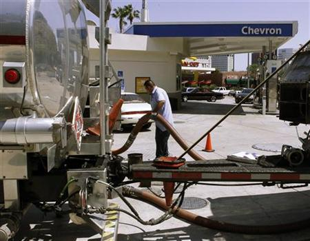 A gasoline tanker driver moves a hose as he fills tanks at a Chevron petrol station in Los Angeles, California April 11, 2011. REUTERS/Fred Prouser