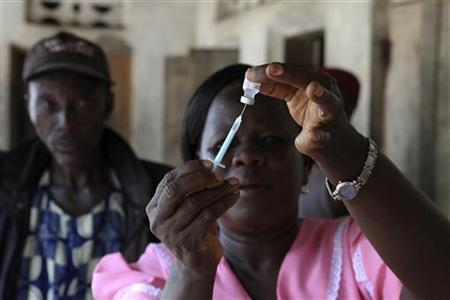 A health worker draws a dosage of vaccine into a syringe during a house call in the village of Kandor outside the town of Bo in the southeast region of the West African country May 24, 2011. REUTERS/Simon Akam