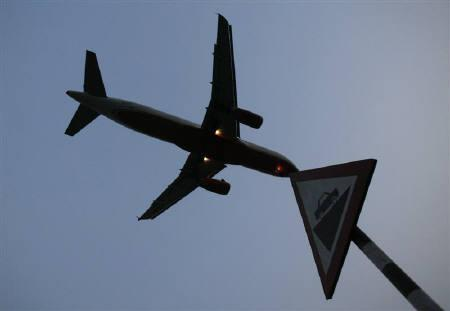 A plane prepares to land at an airport in New Delhi June 4, 2008. Global airlines cut their 2011 profit forecast by more than half to $4 billion on Monday as high oil prices and turmoil in Japan, North Africa and the Middle East weigh on the industry's recovery. REUTERS/Adnan Abidi/Files
