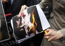 <p>Демонстрант сжигает фотографию президента Сирии Башара аль-Ассада перед сирийским консульством в Стамбуле 13 мая 2011 года. Франция готова просить Совет безопасности ООН проголосовать за проект резолюции, осуждающей жесткое подавление антиправительственных демонстраций в Сирии вопреки угрозам России наложить на него вето, заявил в понедельник глава французского МИДа Ален Жюппе. REUTERS/Osman Orsal</p>
