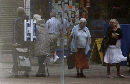 Shoppers are reflected in the window of an empty retail unit in Manchester, June 7, 2011. REUTERS/Phil Noble