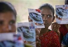 <p>Hemalatha (C) and other loan borrowers show pass books given to them by a micro finance company at Ibrahimpatnam, on outskirts of the southern Indian city of Hyderabad, May 19, 2011. REUTERS/Krishnendu Halder</p>