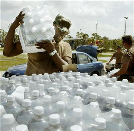 Sgt. Michael Bishop with the Florida Nation Guard prepares to hand out bottled water to people devastated by Hurricane Jeanne in Sebastian, Florida on September 27, 2004. REUTERS/Charles W. Luzier