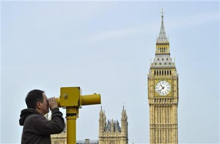 A man looks through a telescope opposite Big Ben and the Houses of Parliament, in central London May 6, 2011. REUTERS/Toby Melville