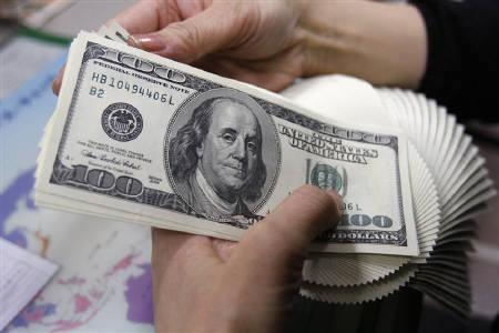 An employee of an money exchange counts U.S. dollar bills in Tokyo November 27, 2009.  REUTERS/Yuriko Nakao/Files