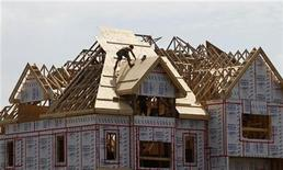 <p>A builder works on the the roof of a new home under construction in the Montreal suburb of Brossard August 10, 2010. REUTERS/Shaun Best</p>