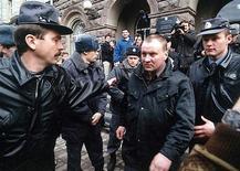 <p>Юрий Буданов (в центре) выходит из здания суда в Ростове-на-Дону, 5 марта 2001 года. Разжалованный полковник-танкист Юрий Буданов, осужденный за похищение и убийство чеченской девушки, застрелен в пятницу в Москве, сообщили правоохранительные органы. REUTERS/Str Old</p>