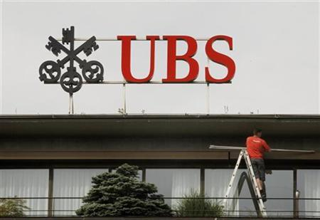 A worker stands on a ladder under the logo of Swiss bank UBS at the company's headquarters in Zurich May 26, 2011. REUTERS/Arnd Wiegmann