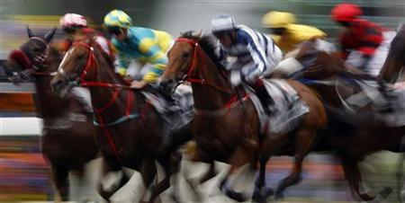 Jockey Darren Beadman (C) riding ''Packing Winner'' races along with other horses during the 2,000-metre Audemars Piguet QEII Cup Group One race at Shatin racetrack in Hong Kong May 1, 2011. REUTERS/Bobby Yip