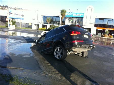 A car sinks into a hole caused by an earthquake in the southern New Zealand city of Christchurch June 13, 2011. REUTERS/Tim Kelleher/Handout