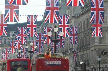 In this file picture, a tourist photographs Union flags hung along Regent Street in celebration of the forthcoming royal wedding between Prince William and Kate Middleton in London April 19, 2011. REUTERS/Toby Melville