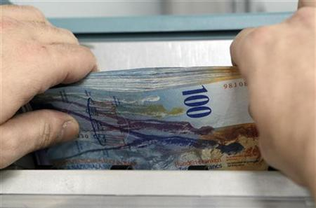 An employee handles 100 Swiss Franc notes in the treatment centre of the Canton of Vaud Bank near Lausanne February 17, 2011. REUTERS/Denis Balibouse