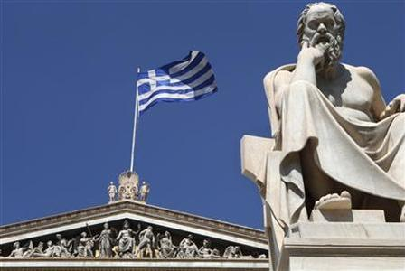 A Greek flag flutters behind a statue of ancient philosopher Socrates at the the Academy of Athens July 23, 2010. REUTERS/John Kolesidis