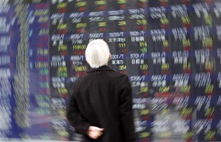 A man looks at a screen displaying stock prices in Tokyo March 16, 2011. REUTERS/Issei Kato