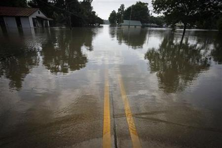 Water from the bulging Mississippi River covers a road near flooded homes and businesses in St. Francisville, Louisiana May 21, 2011. REUTERS/Lee Celano
