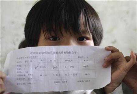 A child holds a laboratory sheet showing high levels of lead in her blood at a village in Wugang, Hunan province August 18, 2009. REUTERS/China Daily