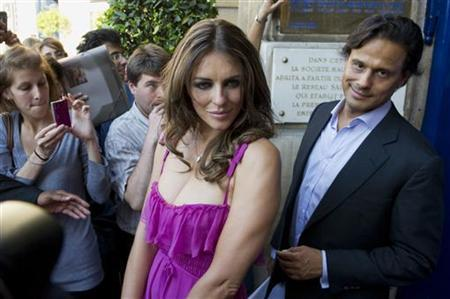 British model Elizabeth Hurley (L) and her husband, Indian businessman Arun Nayar leave after the Valentino fashion house Fall/Winter 2010-2011 Haute Couture show in Paris July 7, 2010. REUTERS/Gonzalo Fuentes