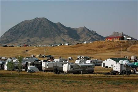 Bear Butte, which some Native Americans consider sacred ground, looms behind campers and a bar during the Black Hills Motor Classic motorcycle rally in Sturgis, South Dakota August 6, 2006. REUTERS/Jonathan Ernst