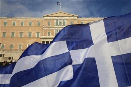 A protester raises Greek flag in front of the parliament during a rally against a new austerity package at Athens' Syntagma (Constitution) square June 11, 2011. REUTERS/Pascal Rossignol