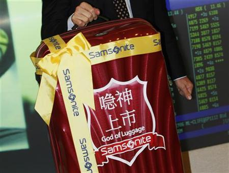 Chairman and CEO of Samsonite International Tim Parker (R) poses with a suitcase -- a souvenir for the Hong Kong Stock Exchange, during the trading debut of Samsonite International in Hong Kong June 16, 2011. Shares of Samsonite International SA , the world's biggest luggage maker, dropped as much as 10.6 percent in its trading debut on Thursday, underscoring tepid investor appetites for IPOs in Hong Kong. REUTERS/Bobby Yip