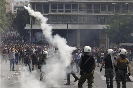 Policemen throw tear gas at protesters during riots around Constitution (Syntagma) square in Athens June 15, 2011. Greek Prime Minister George Papandreou offered Wednesday to step down and make way for a national unity government if the opposition agreed on a clear plan on how to proceed with reforms, government sources said. REUTERS/Yiorgos Karahalis (GREECE - Tags: BUSINESS POLITICS CIVIL UNREST)
