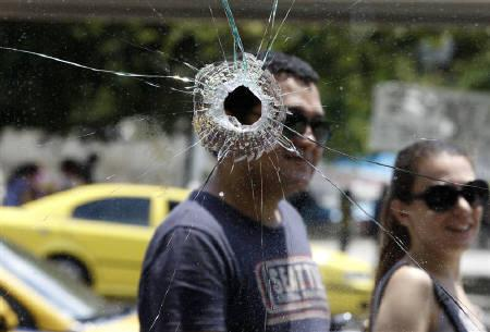 Tourists are seen through a cafe's smashed windows after Wednesday's riots in Athens' central Syntagma (Constitution) Square June 16, 2011. REUTERS/Yannis Behrakis