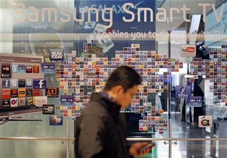 A man uses his smartphone in front of a showroom of Samsung Electronics in Seoul January 28, 2011. REUTERS/Lee Jae-Won
