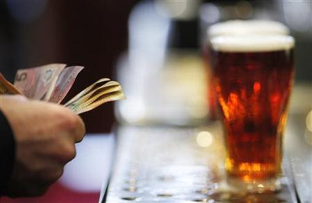 A customer pays for a Fosters beer at the Occidental Hotel in central Sydney June 21, 2011. REUTERS/Tim Wimborne
