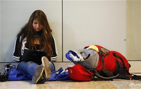 German backpacker Lisa Berkemeyer, a stranded passenger headed to Brisbane, uses her laptop at the Qantas domestic terminal in Sydney's airport June 21, 2011. An ash cloud from a volcano in Chile has wreaked havoc on Australian flights and prompted the country's leading airline Qantas to cancel flights to and from the nation's biggest airports on Tuesday and Wednesday. REUTERS/Daniel Munoz