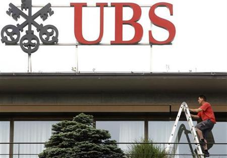 A worker climbs on a ladder under the logo of Swiss bank UBS at the company's headquarters in Zurich May 26, 2011. REUTERS/Arnd Wiegmann