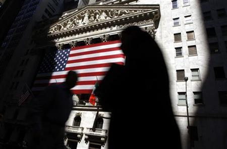 The sun lights the exterior of the New York Stock Exchange, as people walk past on the shadowed street, July 16, 2008. REUTERS/Chip East