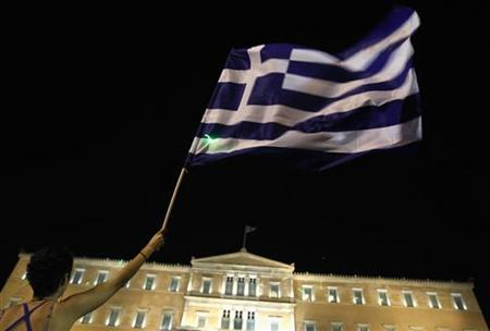 A protester raises a Greek flag during a rally against a new austerity package in front of the parliament in Athens June 21, 2011. REUTERS/Yiorgos Karahalis