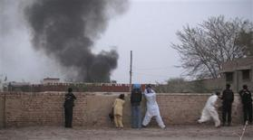 <p>Police and members of the media take their positions as smoke rises from a police station after it was attacked by gunmen in Dera Ismail Khan on June 25, 2011. REUTERS/Mustansar Baloch</p>