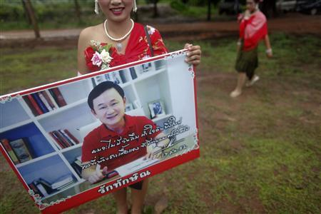 A girl wearing a traditional costume holds a placard displaying a picture of ousted premier Thaksin Shinawatra during a religious ceremony at a temple in the village of Suan Mon near Udon Thani in northeastern Thailand June 25, 2011. Regional leaders of Thailand's red-shirt protest movement held a traditional Buddhist ceremony to launch 38 villages to be designated as the ''Red Shirt Village of Democracy''. The red shirts, supporters of Thaksin, have been branding hundreds of villages as red to rally behind Thaksin's sister, Yingluck, who is leading the opposition ahead of July 3 general elections. REUTERS/Damir Sagolj