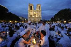 <p>People attend the White Dinner event in front of the Notre Dame Cathedral in Paris June 16, 2011. REUTERS/Gonzalo Fuentes</p>