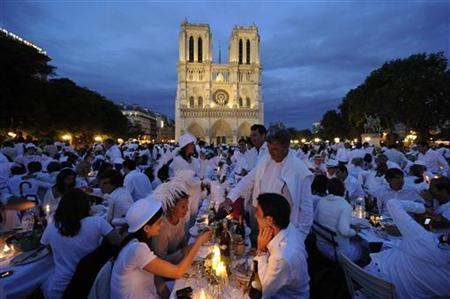 People attend the White Dinner event in front of the Notre Dame Cathedral in Paris June 16, 2011. REUTERS/Gonzalo Fuentes