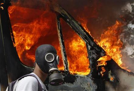 A protester wearing a gas mask walks beside a burning van during violent protests against austerity measures in Athens, June 28, 2011. REUTERS/Yannis Behrakis