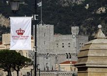<p>A flag announcing the wedding of Prince Albert II of Monaco and his fiancee Charlene Wittstock is seen with Monaco Palace in the background June 27, 2011. REUTERS/Eric Gaillard</p>