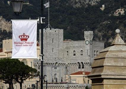 A flag announcing the wedding of Prince Albert II of Monaco and his fiancee Charlene Wittstock is seen with Monaco Palace in the background June 27, 2011. REUTERS/Eric Gaillard